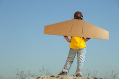 Happy boy with cardboard boxes of wings against sky dream of fly Royalty Free Stock Photography