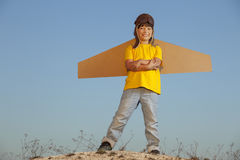 Happy boy with cardboard boxes of wings against sky dream of fly Royalty Free Stock Images