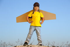 Happy boy with cardboard boxes of wings against sky dream of fly Stock Photos