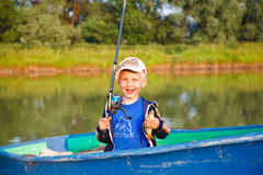 Happy boy with catch. Smiling boy in a boat with carp in one hand and fishing-rod in another stock image
