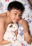 Happy boy with cats. Happy asian boy with cats lieng in bed Royalty Free Stock Photo
