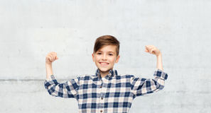 Happy boy in checkered shirt showing strong fists Stock Photo