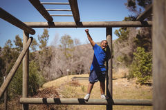 Happy boy cheering on monkey bar during obstacle course. In boot camp Stock Image