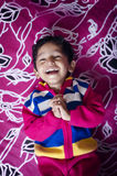 Happy boy child laughing with folded hands on bed Royalty Free Stock Photo