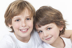 Happy Boy Children Brothers Smiling Together. White background studio photograph of young happy boy children brothers smiling together Royalty Free Stock Photo