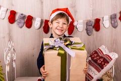Happy boy with christmas gift near Christmas tree stock photos