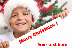 Happy boy with christmas hat and white banner Stock Photo