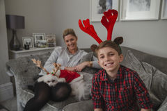 Happy Boy At Christmas Time. Happy little boy is smiling for the camera while wearing christmas antlers. His mother is sitting next to him with their pet dog on Stock Photography