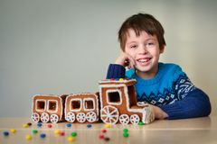 Happy boy with christmas train made of gingerbread Royalty Free Stock Photo
