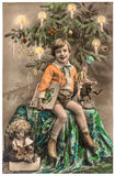 Happy boy with christmas tree, gifts and vintage toys. Antique picture with original film grain and scratches stock photos