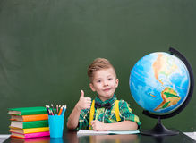Happy boy in classroom showing thumbs up Royalty Free Stock Photo