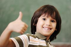 Happy boy in classroom with thumb. Up: green board behind Stock Images