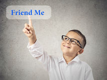 Happy boy clicks on friend me button. Closeup portrait happy, smiling child touching, pressing friend me button, icon on touchscreen display isolated grey Royalty Free Stock Image