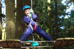 Happy boy climbing in adventure park Stock Images
