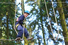 Happy boy climbing in adventure park Royalty Free Stock Photography