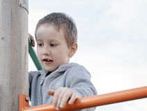 Boy climbing on children playground outdoors. Pre-school child having fun on playground. Kid playing on children playground royalty free stock photos