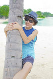 Happy boy is climbing on palm tree. In Sentosa Royalty Free Stock Image