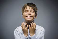 Happy boy. Closeup Portrait of handsome teen pleading or beging on grey background Stock Images