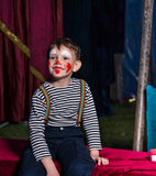Happy boy with clown make up sitting on a stage Stock Photo
