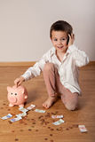 Happy boy collecting money in his piggy bank and talking phone Royalty Free Stock Photography