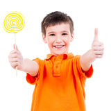 Happy boy with colored candy showing thumbs up sign. Stock Photography