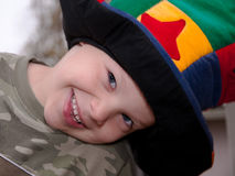 Happy Boy With Colorful Hat. This happy boy is smiling while playing with a brightly colored hat Stock Image