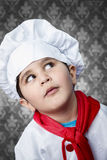 Happy boy cook in uniform over vintage  background funny look Royalty Free Stock Image