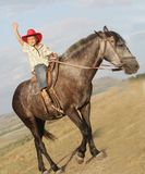 Happy boy in cowboy hat riding horse outdoors. Young happy boy in cowboy hat riding horse on natural background Royalty Free Stock Photography
