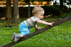 Happy boy creeping on the ladder Royalty Free Stock Photos