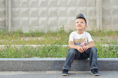 Happy boy on a curb. Cute stylish preschooler sitting on a road curb outside Royalty Free Stock Photography