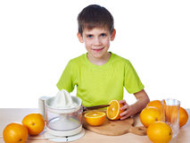 Happy boy cutting orange for juicer  Stock Photos