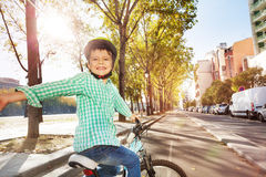 Happy boy cycling on bicycle lane in town Royalty Free Stock Photography