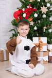 Happy boy in deer costume with gift boxes and Christmas tree Stock Photography