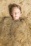 Happy boy dig oneself in the sand Royalty Free Stock Images