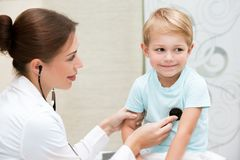 Happy boy at the doctor. Happy brave little boy at the doctor, young female pediatrician using stethoscope listening babys lungs, enjoying visits to doctor Royalty Free Stock Photos