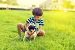 Happy boy with dog. Happy Asian boy playing with his dog in garden Stock Photo