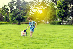 Happy boy with dog. Happy Asian boy playing with his dog in garden Royalty Free Stock Image