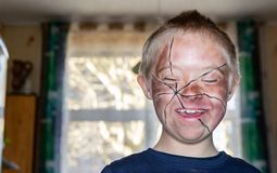 Defect,childcare,medicine and people concept. Happy boy with down syndrome, prepared and painted for home theater stock photos