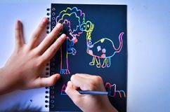The boy draws on a note colorful,Happy time. Happy boy draws on a Scratch note colorful stock photo