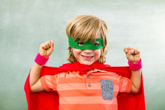 Happy boy dressed as superhero in classroom. Portrait of happy boy dressed as superhero in classroom Royalty Free Stock Images
