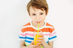 Happy boy drinking orange juice in kitchen looking at camera. Portrait of a young boy who is drinking juice in the white background Royalty Free Stock Photos