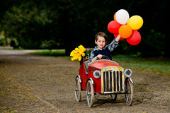 Happy boy driving old toy car with colorful balloons. And yellow flowers Stock Photos