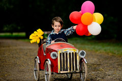 Happy boy driving old toy car with colorful balloons. And yellow flowers Royalty Free Stock Images