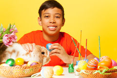 Happy boy with Easter eggs and rabbit on  table Royalty Free Stock Photo