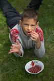 Happy boy eating berries on the grass. stock image