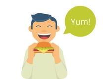 Happy boy eating a big hamburger Stock Image