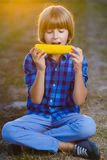 Happy boy eating healthy corn on the cob Royalty Free Stock Photos