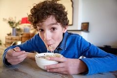 Happy boy eating noodles at home royalty free stock photo