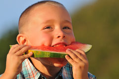 Happy boy eating sweet Watermelon Stock Image