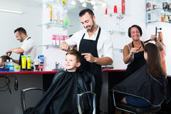 Happy boy in elementary school age getting hairdo of man royalty free stock photo